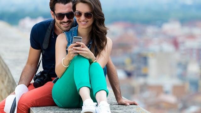 Casal usando o celular em viagem