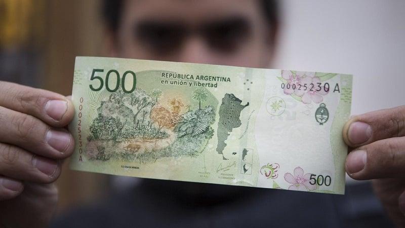 Pessoa segurando nota peso argentino