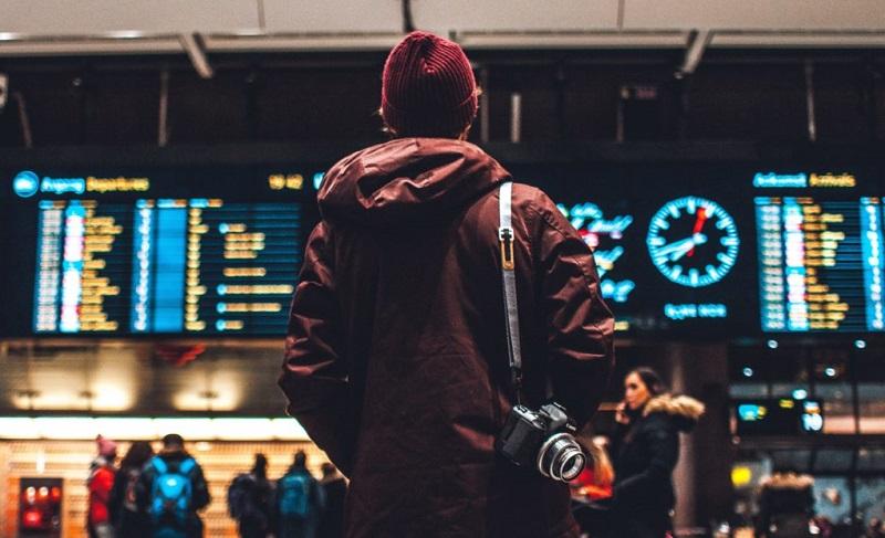 Menino olhando painel de voos em aeroporto